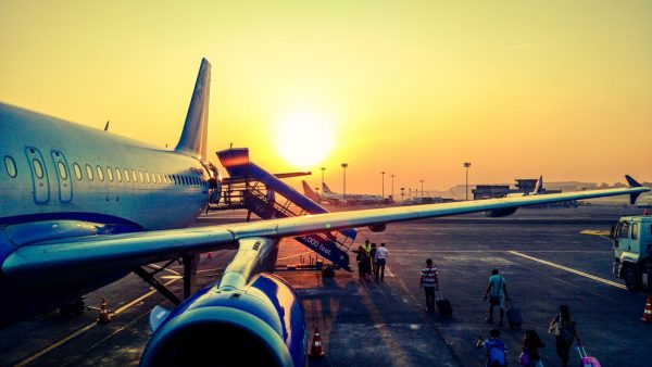 Passenger jet boarding on tarmac with Sunset